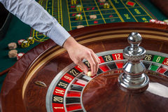Roulette wheel and croupier hand with white ball in casino Royalty Free Stock Image