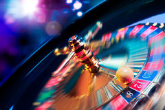 Roulette wheel in motion with a bright and colorful background. High contrast image of casino roulette in motion Stock Photography