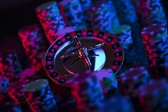 Gambling theme. Place for text and typography. Roulette wheel and stack of poker chips on glass table. Colorful bokeh background stock photography