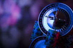 Gambling theme. Place for text and typography. Roulette wheel and stack of poker chips on glass table. Colorful bokeh background stock images