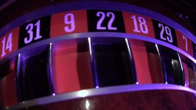 Roulette wheel starts running with white ball. Zero. Close up. Usual roulette wheel running with fallen white ball, top view, spinning wheel with ball at zero in stock footage