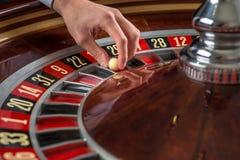 Roulettekessel- und Croupierhand mit weißem Ball im Kasino Stockfotografie