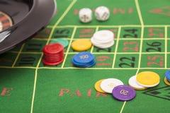 Rouletten i kasino, gå i flisor och tärnar att stapla på en grön filt Arkivbilder