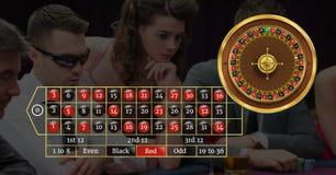 Roulettmanöverenhet och spelare i kasino arkivfoto