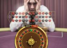 Roulettmanöverenhet och stressad angelägen man i kasino royaltyfri bild