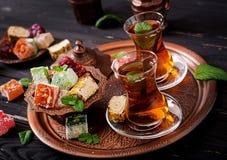 Roulez avec de divers morceaux de lokum de plaisir turc et de thé noir Image libre de droits