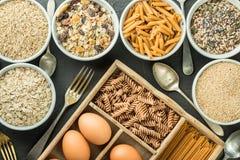 Roulez avec des hydrates de carbone et les oeufs entiers sains, kamut, graines, avoine, riz brun, spaghetti Image stock