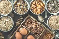 Roulez avec des hydrates de carbone et les oeufs entiers sains, kamut, graines, avoine, riz brun, spaghetti Photographie stock libre de droits