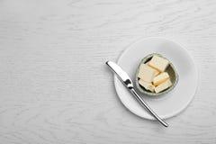 Roulez avec du beurre et le couteau frais savoureux sur la table en bois Photo stock