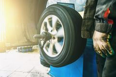 Roulez l'équilibrage ou la réparation et changez le pneu de voiture au garage automatique de service ou l'atelier par le mécanici images stock