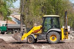 Roulez l'excavatrice de chargeur avec le sable arrière de chargement de houe images stock