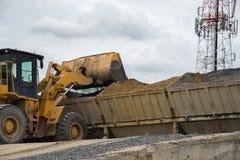 Roulez l'excavatrice de chargeur déchargeant le sable avec de l'eau pendant la terre MOIS Image stock