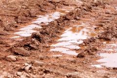 Roulez la trace sur la route, le magma et la boue après pluie Traces sur le sol du tracteur, excavatrice, voiture, voies des véhi Photos stock