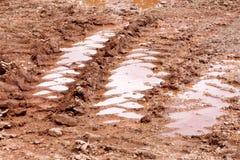 Roulez la trace sur la route, le magma et la boue après pluie Traces sur le sol du tracteur, excavatrice, voiture, voies des véhi Photographie stock libre de droits