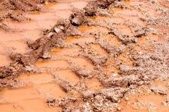 Roulez la trace sur la route, le magma et la boue après pluie Traces sur le sol du tracteur, excavatrice, voiture, voies des véhi Photographie stock