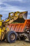 Roulez le minerai de chargement de chargeur dans le camion à benne basculante aux nuages de pluie à ciel ouvert photographie stock libre de droits