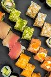 Roulis de sushi d'une plaque noire Images stock