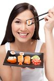 Roulis de sushi de sourire de fixation de femme avec baguettes Images stock