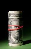 Roulis des 100 dollars serré avec une bande élastique rouge. Image stock
