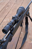 Round in. High powered rifle with scope on a tripod , action is opened and a round in chamber royalty free stock photo