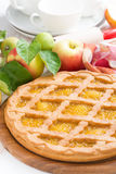 Round apple pie on a white wooden table, vertical Royalty Free Stock Images