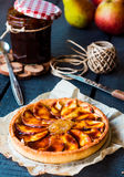 Round apple tart with pear jam and caramel, vertically Royalty Free Stock Photos