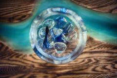 Aquarium with blue small fish. Round aquarium with blue small fish on wooden table with glass stock photos