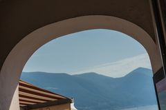 Round arch mountain view in summer with house roof in mediterranean city switzerland italy. Ascona Stock Images