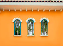 Round arch window on the orange wall Stock Photo