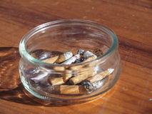 Round ashtray with cigarettes on an wooden table. Glassy ashtray with cigarettes on a wooden table Royalty Free Stock Photos