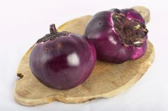 Round aubergines. Close-up of a couple of violet round aubergine on a cutting board Royalty Free Stock Images