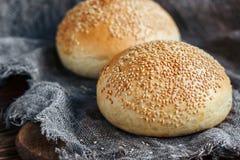 Round babeczka, sezamowa babeczka, chlebowe rolki Smakowity hamburgeru chleb z sezamem na drewnianym, burlap tło Świeżo piec hamb zdjęcia royalty free