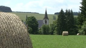 Round bale of hay in a meadow, background church tower stock video