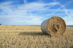 Round bale of straw. With blue sky and clouds Royalty Free Stock Photos