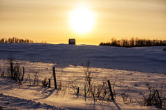A round bale on top of a snow topped hill. Fenced pasture with a round bale on a snow covered hill at sunset Stock Photography