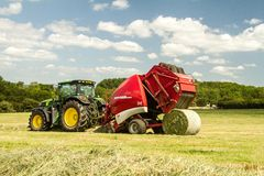A round baler discharges a hay bale during harvesting Stock Photos