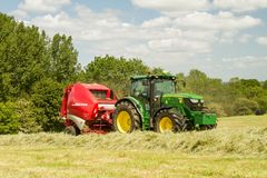 A round baler discharges a hay bale during harvesting Royalty Free Stock Photo