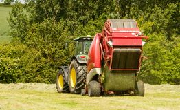A round baler discharges a hay bale during harvesting Royalty Free Stock Image