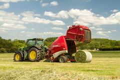 A round baler discharges a hay bale during harvesting Royalty Free Stock Photos