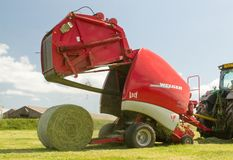 A round baler discharges a hay bale during harvesting Stock Images
