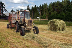 Round baler dumping a freshly rolled hay bale. Royalty Free Stock Images