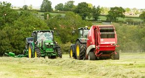 A round baler and plastic bale wrapper during harvesting Stock Image