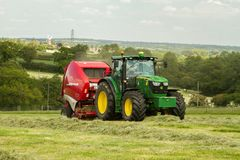 A round baler pulled by a John Deere during harvesting Stock Images