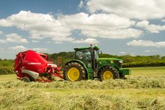 A round baler pulled by a John Deere during harvesting Royalty Free Stock Photo