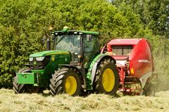 A round baler pulled by a John Deere during harvesting Stock Photos