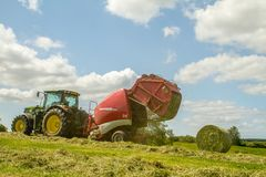 A round baler pulled by a John Deere during harvesting Royalty Free Stock Photos