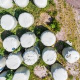 Round bales with silage as animal feed, wrapped in foil, vertical aerial view from above. Made with drone Stock Image