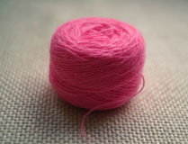 A round ball of pink thread on the white background of the canvas Stock Photo