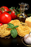 Round balls of pasta with cheese, tomatoes,basil,olive oil on black Royalty Free Stock Photography