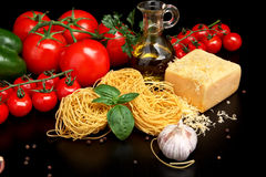 Round balls of pasta with cheese,tomatoes,basil,olive oil on black Royalty Free Stock Photos